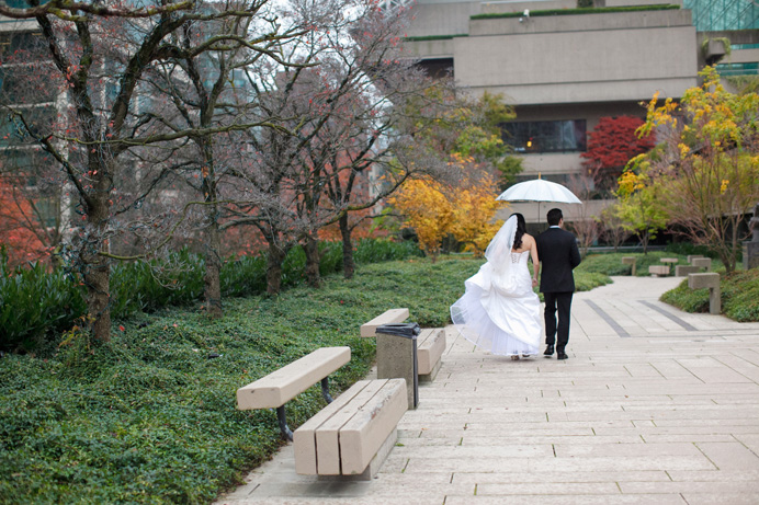 Walking in the rain on their wedding day
