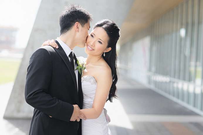 Groom kissing bride before reception at the Westin Wall Centre Airport