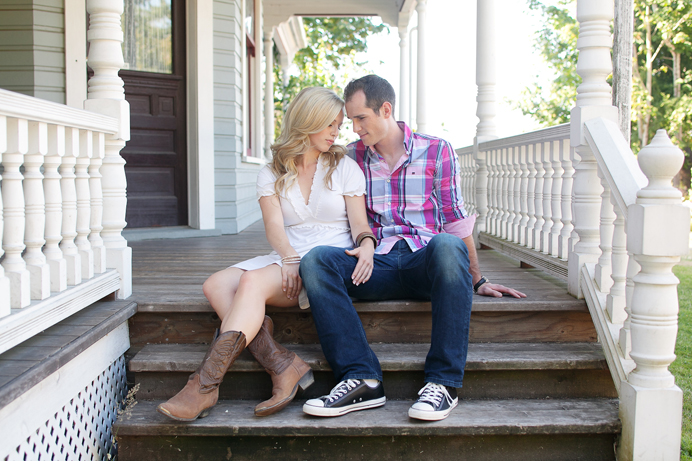 Couples photo on the porch of a farmhouse