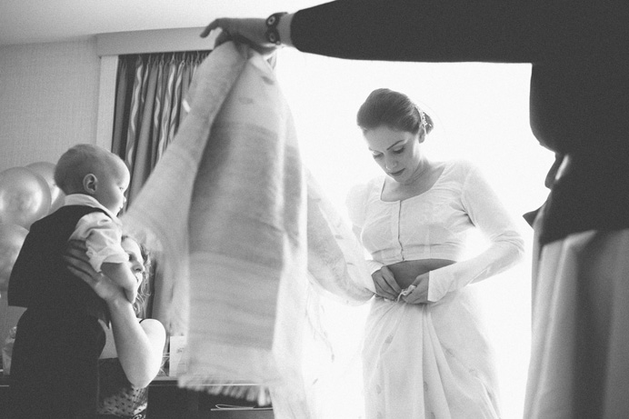 Bride putting on a sari before the wedding