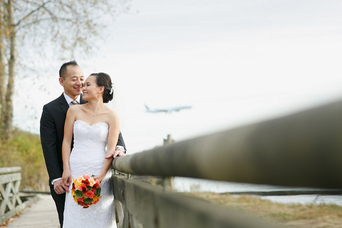 Bride and groom with airplane behind