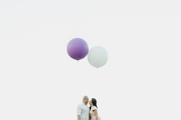 couple with balloons kissing