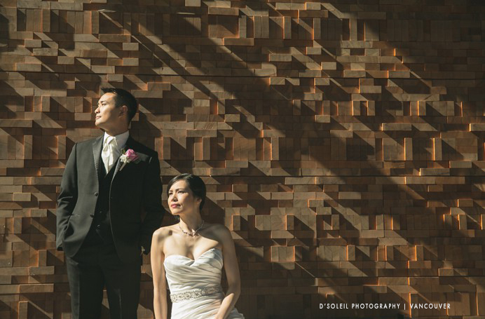 Bride and groom in front of the wall of wood at the Vancouver Convention Centre