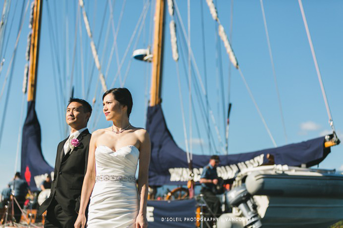 bride and groom at coal harbour in front of sailing boat