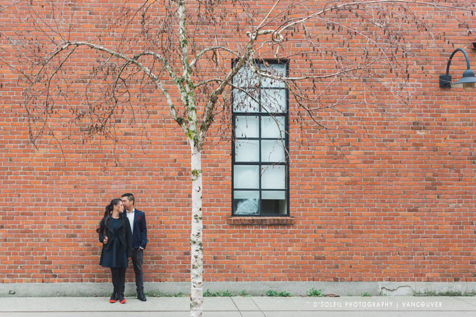 Couple standing at brick wall in Yaletown