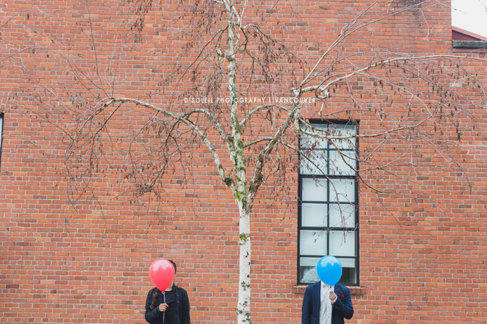 Couple standing at brick wall with balloons in Yaletown