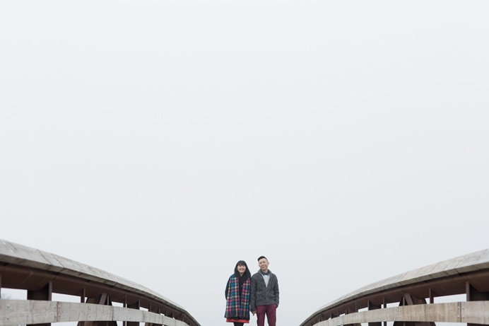 couple standing on rustic bridge