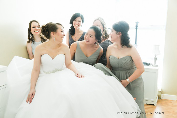 bridal wedding photo with bridesmaids on bed