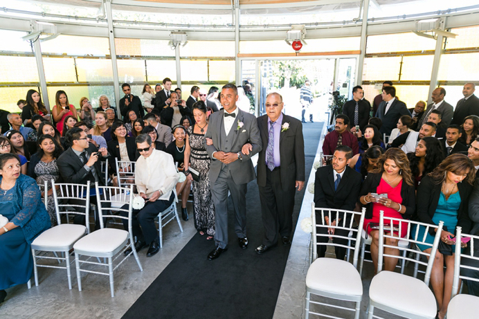 Grooms walks down aisle with parents