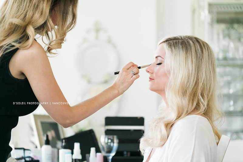 Makeup artist working wedding with bride