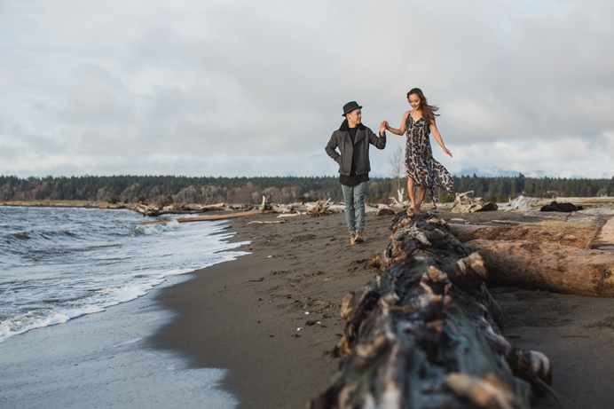 Walking on log at beach engagement session